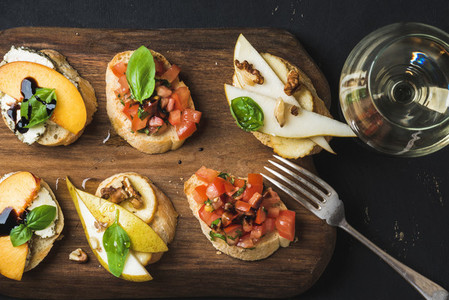 Bruschetta set with glass of white wine over dark background