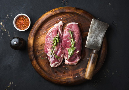 Raw duck breast with rosemary  spices on dark wooden tray