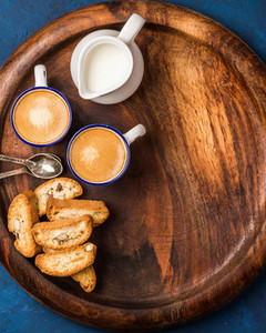 Coffee espresso  cookies and milk on wooden serving round board