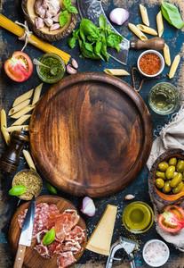 Italian food cooking ingredients on dark plywood background  copy space
