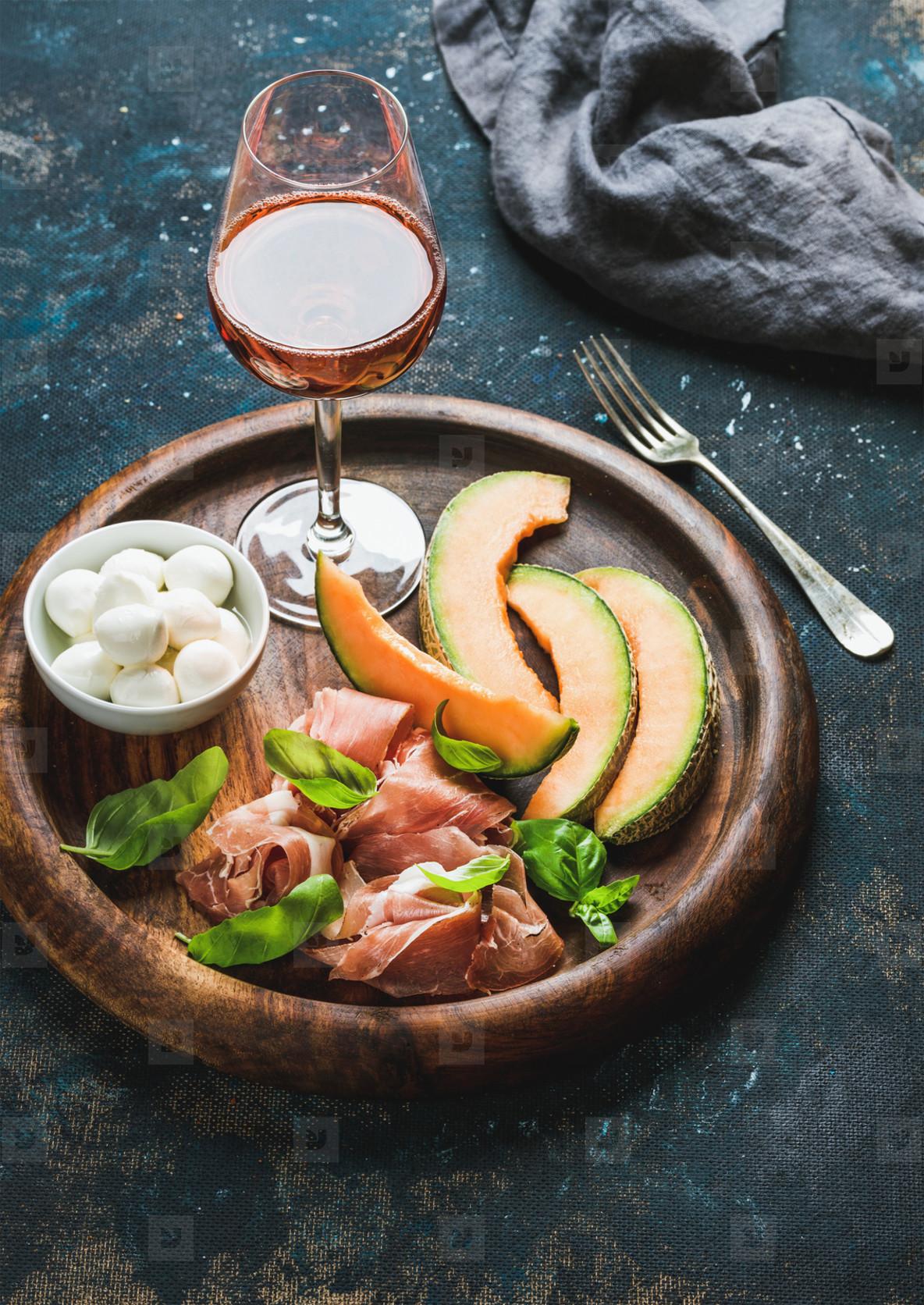 Prosciutto  cantaloupe melon  mozzarella cheese and glass of rose