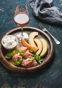 Prosciutto  cantaloupe melon  mozzarella cheese and glass of rose