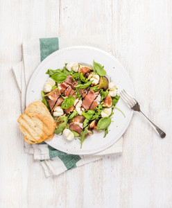 Prosciutto arugula basil figs salad and glass of red wine