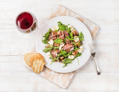 Prosciutto  arugula  figs salad with bread and glass of red
