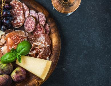 Italian antipasti snack for wine on wooden tray  dark background
