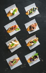 Italian crostini with various toppings on white baking paper