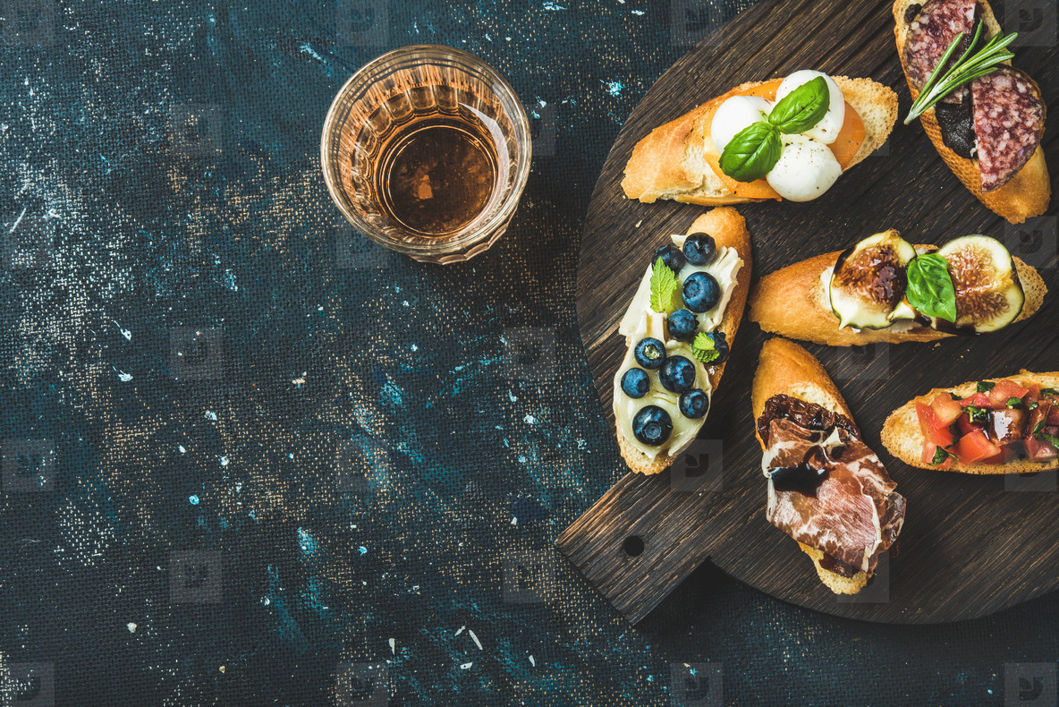 Italian crostini and glass of rose wine over dark background