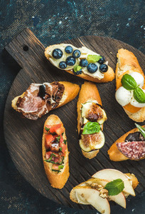 Italian crostini with various toppings on round wooden serving board