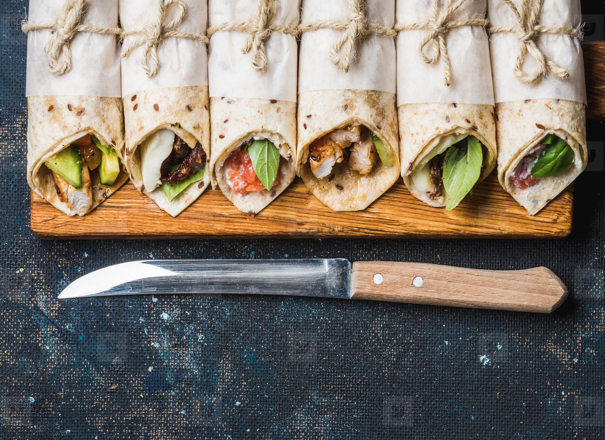 Tortilla wraps with different fillings on dark grey concrete background