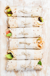Tortilla wraps with various fillings on shabby white wooden background