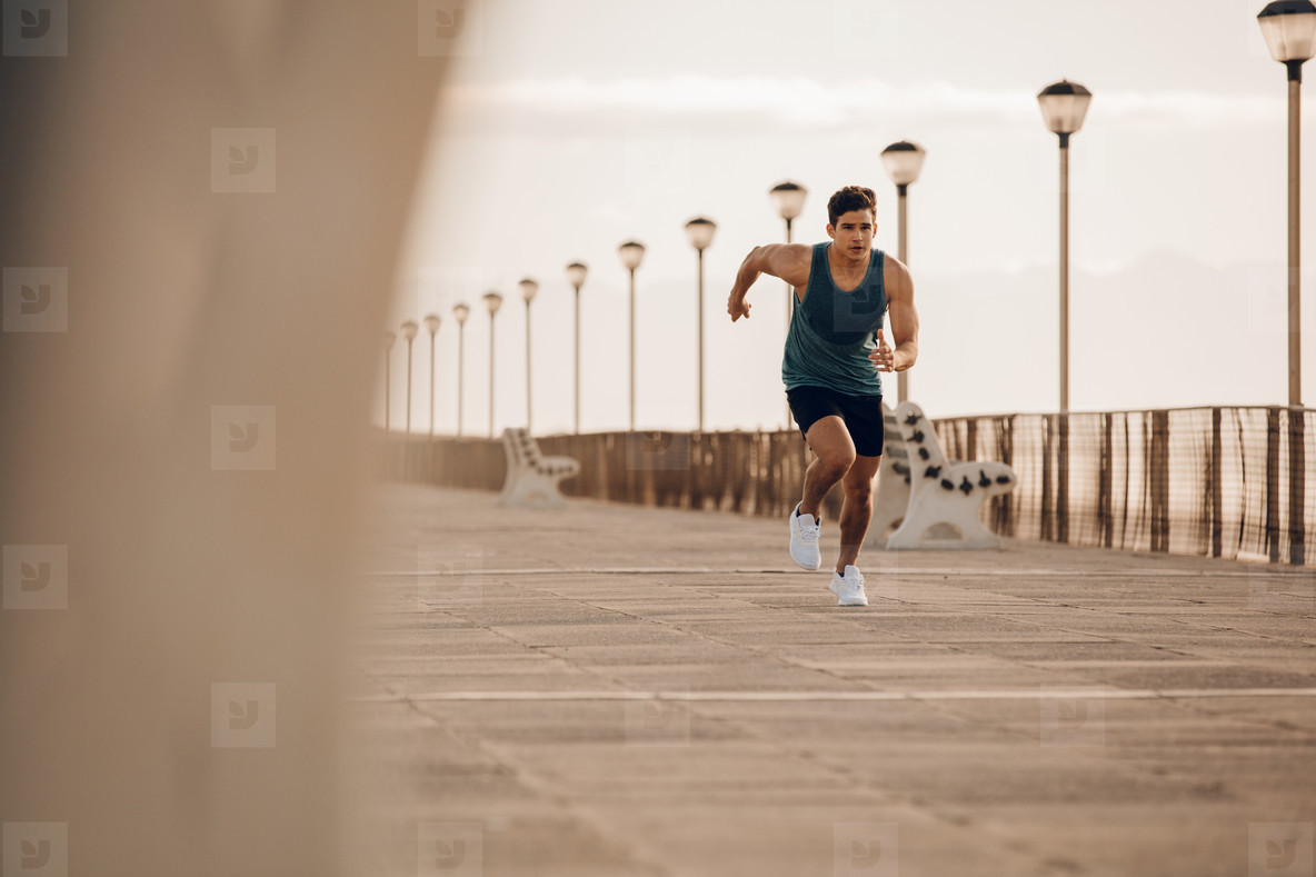 Fit young man running fast on the promenade