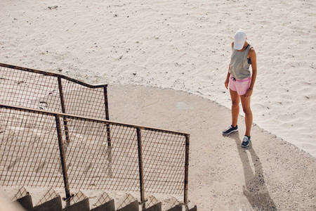 Young woman standing by a staircase at the beach