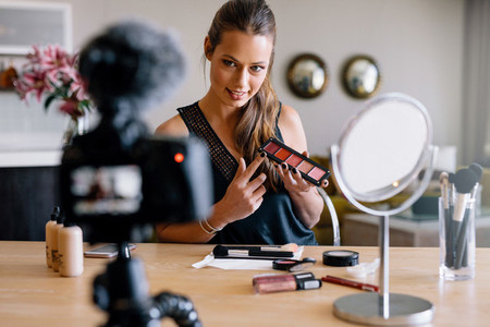 Young female vlogger recording a make up broadcast for her vlog