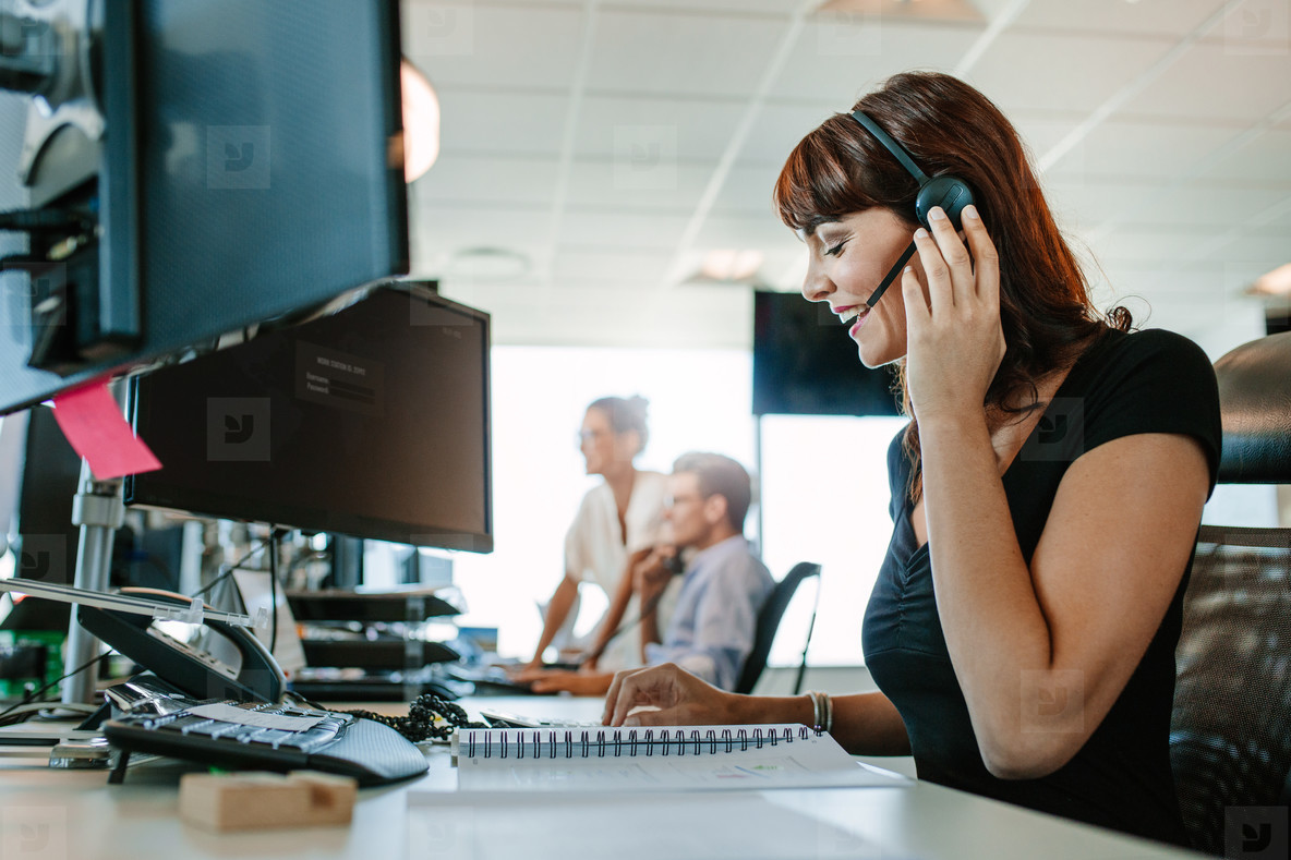 Happy mature business woman talking on headset