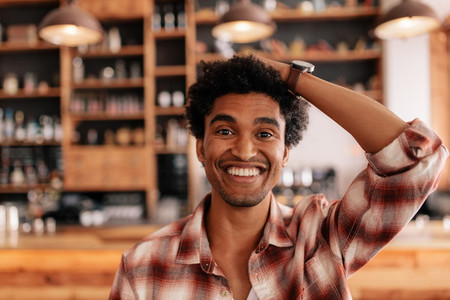 Young man smiling in a cafe with hand on head