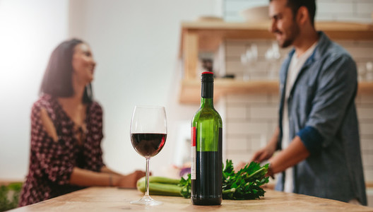 Wine on kitchen counter with couple cooking in background