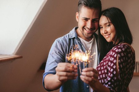 Loving young couple celebrating with sparklers at home
