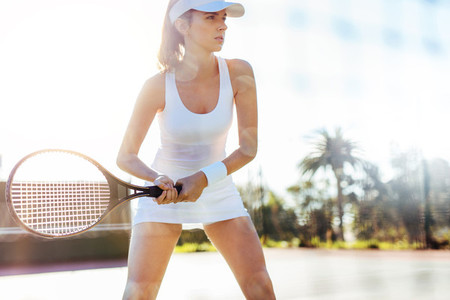 Young sportswoman playing on tennis court