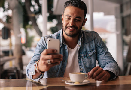 Man in coffee shop reading text message on mobile phone