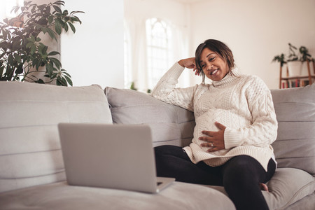 Happy pregnant woman on sofa using laptop