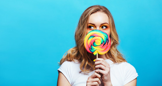 Young woman holding lollipop in front of her mouth