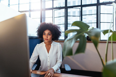 Young african woman working late in office