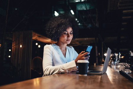 Businesswoman working late and using mobile phone