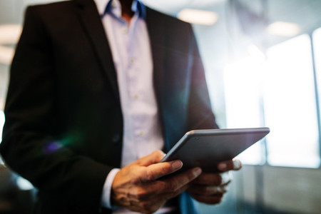 Male hands using digital tablet in office