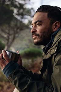 Male hiker taking rest outdoors with a cup of coffee