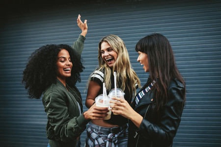 Group of female friends having fun with ice coffee