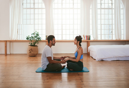 Beautiful young couple doing yoga at home