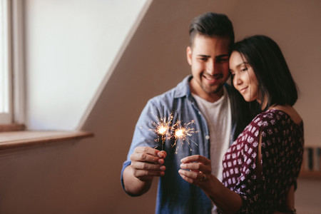 Beautiful young couple celebrating with sparklers