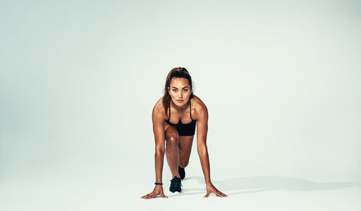 Confident female athlete ready for running