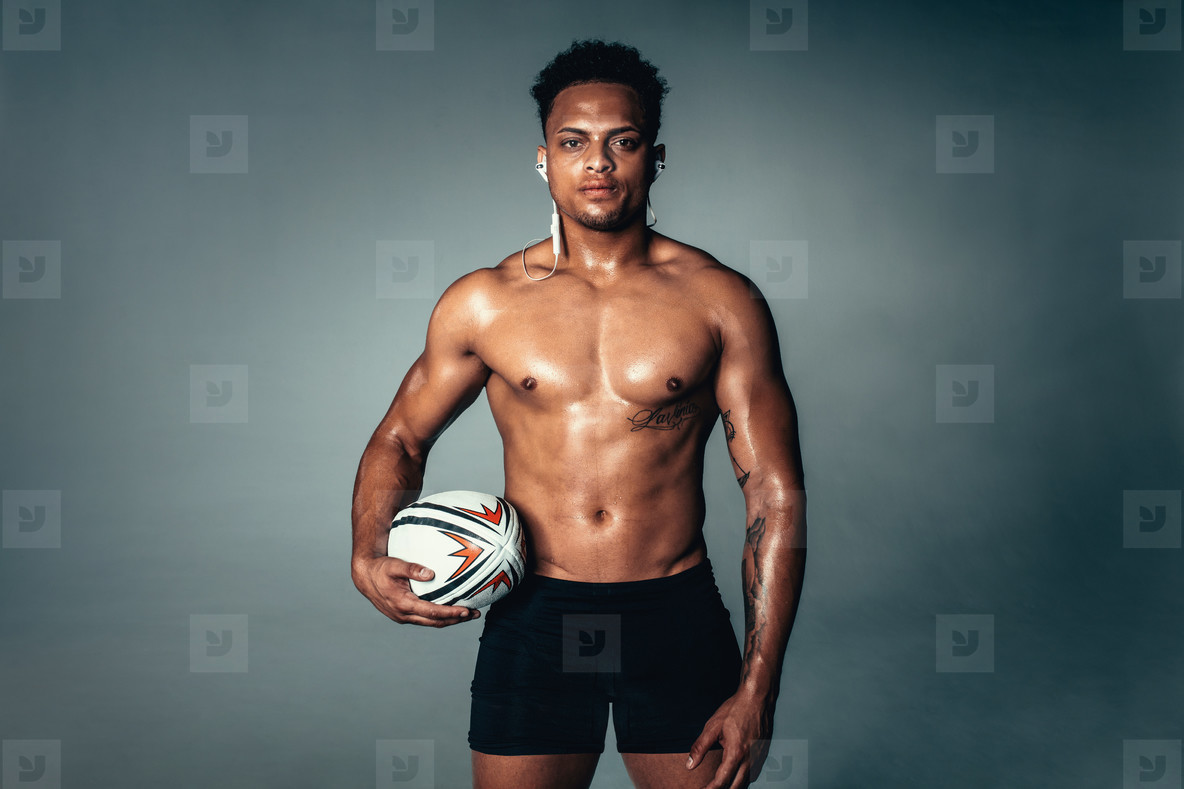 Fit young man holding rugby ball