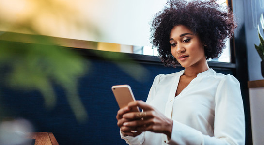Beautiful businesswoman using smart phone in office