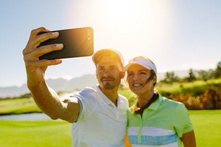 Young couple taking self portrait at golf course