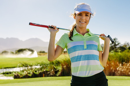 Smiling young female golfer carrying golf club