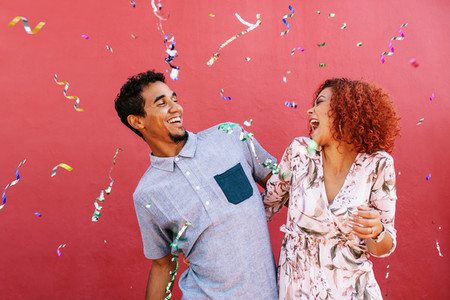 Happy young couple celebrating with confetti in air