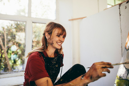 Female artist painting on canvas and smiling