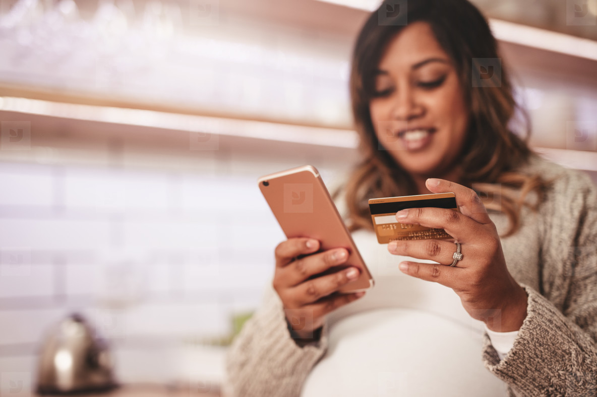 41af25dce1f Photos - Pregnant woman shopping online with credit card and mobile phone -  YouWorkForThem