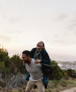 Couple enjoying piggyback ride in countryside