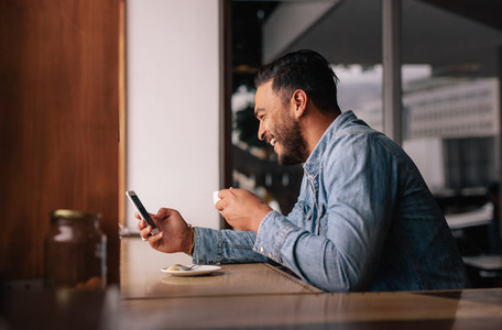 Handsome guy at cafe using smart phone and having coffee