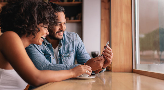 Smiling young couple sitting at coffee shop looking at mobile ph