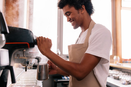 Happy young man preparing coffee at counter
