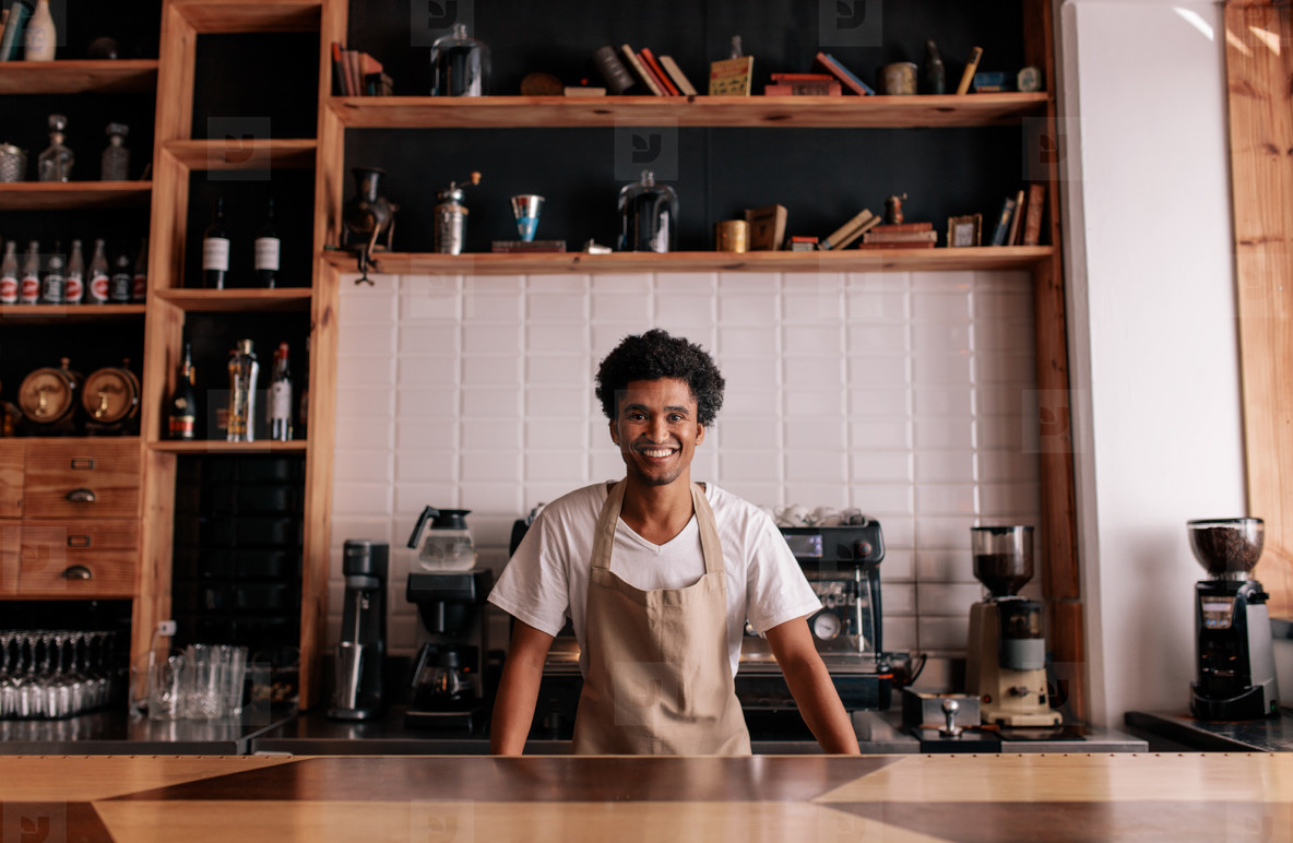 Professional barista standing at cafe counter