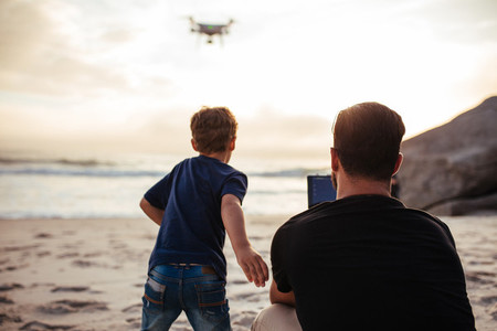 Father and son on the beach flying drone