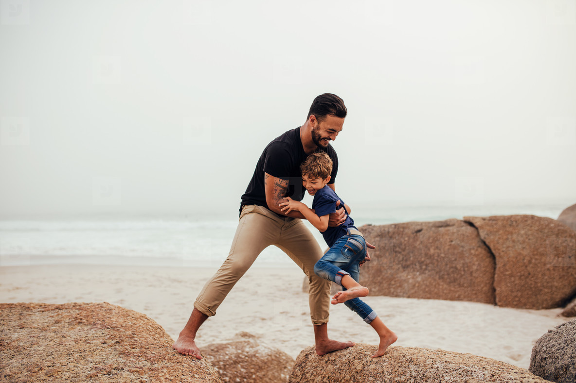 Father playing with son on the beach