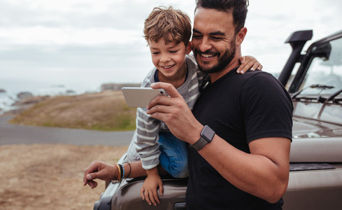 Father and son on road trip using smart phone