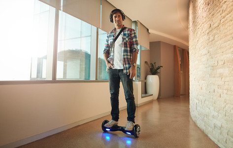 Young man on an electrical self balancing scooter in office