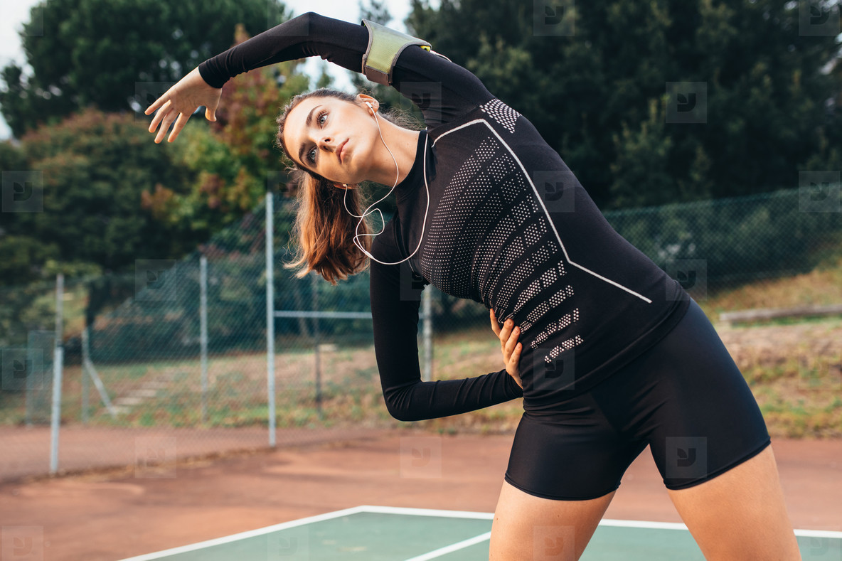 Sportswoman doing stretching workout on tennis court